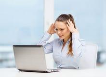 Donna sollecitata con il computer portatile Immagine Stock