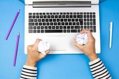 Donna sollecitata con la carta di sgualcitura del computer portatile che prova a fornire la giusta soluzione Immagine Stock