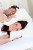 Donna sollecitata con la testa sotto il cuscino Fotografie Stock Libere da Diritti