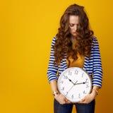 Donna sollecitata isolata sull'orologio giallo della tenuta del fondo Fotografie Stock Libere da Diritti