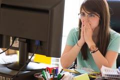 Donna sollecitata sul lavoro con il computer davanti lei Fotografie Stock Libere da Diritti