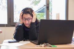 Donna sollecitata sul lavoro con il computer davanti lei Fotografia Stock Libera da Diritti