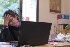Donna sollecitata sul lavoro con il computer davanti lei Immagine Stock Libera da Diritti