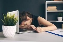 Donna sonnolenta annoiata stanca Impiegato di concetto che dorme al suo scrittorio fotografia stock