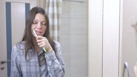 Donna sonnolenta che pulisce i suoi denti nel bagno davanti allo specchio stock footage