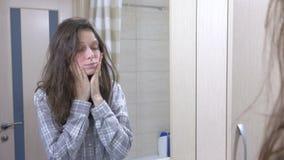 Donna sonnolenta con postumi di una sbornia nel bagno che esamina la sua riflessione nello specchio archivi video