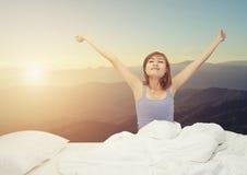Donna sonnolenta stanca che sveglia e che sbadiglia con un allungamento mentre si fotografia stock libera da diritti