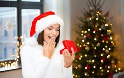 Donna sorpresa in cappello di Santa con il regalo di natale fotografia stock libera da diritti