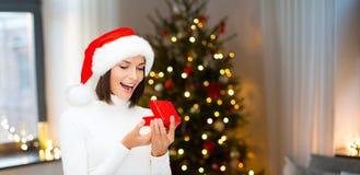 Donna sorpresa in cappello di Santa con il regalo di natale immagini stock