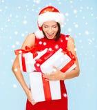 Donna sorpresa in cappello di Santa con molti contenitori di regalo Immagine Stock