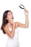 Donna sorpresa che cerca con la lente d'ingrandimento fotografia stock libera da diritti