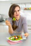 Donna sorpresa che mangia insalata greca e che guarda TV Immagini Stock