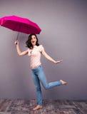 Donna sorpresa che posa con l'ombrello immagini stock libere da diritti
