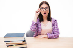 Donna sorpresa che si siede alla tavola con i libri Fotografie Stock