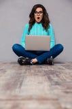 Donna sorpresa che si siede sul pavimento con il computer portatile Immagini Stock Libere da Diritti