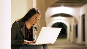 Donna sorpresa che trova gli sguardi contenti online alla macchina fotografica video d archivio