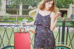 Donna sorpresa con gli insetti facendo uso del telefono cellulare vicino alla bicicletta d'annata Immagine Stock