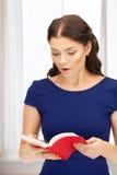 Donna sorpresa con il libro Fotografie Stock
