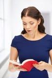 Donna sorpresa con il libro Immagini Stock