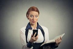 Donna sorpresa con il libro che esamina telefono con emozione disgustosa sul fronte Immagini Stock