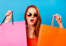 Donna sorpresa della testarossa che tiene i sacchetti della spesa fotografia stock libera da diritti