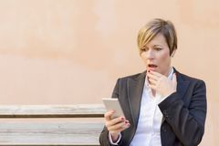 Donna sorpresa di affari che chiama dal telefono all'aperto immagini stock libere da diritti