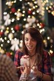 Donna sorpresa e curiosa che riceve il regalo di Natale Immagini Stock