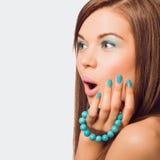 Donna sorpresa giovani che tiene un braccialetto del turchese Fotografia Stock Libera da Diritti