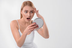 Donna sorpresa osservando la sua pelle facciale fotografia stock libera da diritti