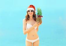 Donna sorridente abbastanza giovane del ritratto di Natale in cappello rosso di Santa con l'ananas sulla spiaggia sopra il mare Fotografie Stock