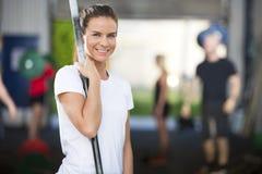 Donna sorridente al centro della palestra di forma fisica Immagini Stock
