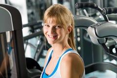 Donna sorridente alla macchina di esercitazione del centro di forma fisica Immagine Stock Libera da Diritti