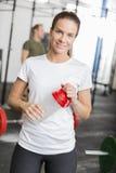 Donna sorridente alla palestra di forma fisica che prende una rottura Fotografie Stock