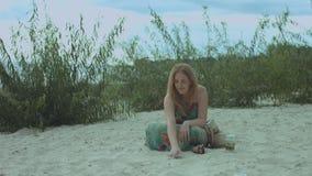 Donna sorridente allegra che attinge sabbia alla spiaggia stock footage