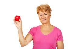 Donna sorridente anziana che tiene il cuore rosso del giocattolo Fotografia Stock