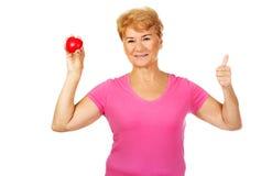 Donna sorridente anziana che tiene il cuore rosso del giocattolo con il pollice su Fotografie Stock Libere da Diritti