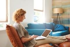 Donna sorridente in appartamento accogliente con il computer portatile immagini stock