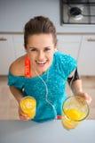 Donna sorridente atletica che tiene frullato appena fatto in cucina Fotografie Stock