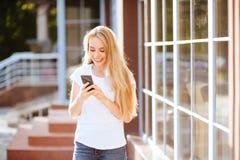 Donna sorridente attraente che per mezzo dello smartphone all'aperto immagini stock libere da diritti