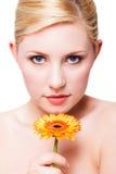 Donna sorridente attraente con un fiore Immagine Stock Libera da Diritti