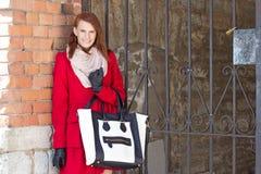Donna sorridente attraente sopra il muro di mattoni rosso Fotografia Stock Libera da Diritti