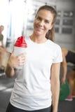 Donna sorridente in attrezzatura di allenamento alla palestra di forma fisica Immagini Stock Libere da Diritti