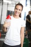 Donna sorridente in attrezzatura di allenamento alla palestra di forma fisica Immagine Stock
