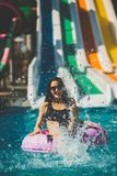 Donna sorridente in bikini che si siede nello stagno sull'anello di gomma immagine stock libera da diritti