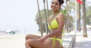 Donna sorridente in bikini giallo che si siede sulla parete video d archivio