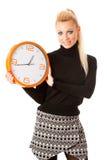 Donna sorridente calma con il grande orologio arancio che non non gesturing attività, enou Fotografie Stock Libere da Diritti