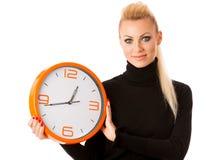 Donna sorridente calma con il grande orologio arancio che non non gesturing attività, enou Fotografia Stock
