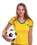 Donna sorridente in camicia brasiliana con calcio fotografie stock libere da diritti