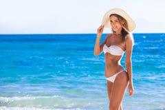 Donna sorridente in cappellino da sole sulla spiaggia del mare fotografia stock