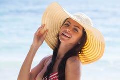 Donna sorridente in cappellino da sole sulla spiaggia del mare immagini stock libere da diritti